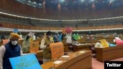 اجلاس کے دوران حزب اختلاف کے اراکین کتبے اٹھائے ہوئے۔