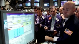 Specialist Jay Woods, right, works with traders on the floor of the New York Stock Exchange, June 28, 2012.