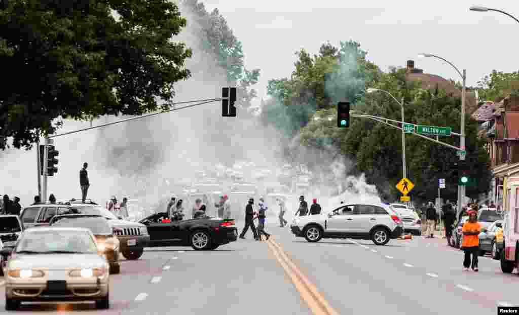 Tear gas rises as police attempt to disperse protesters on Page Avenue after a shooting incident in St. Louis, Aug. 19, 2015.