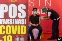 Seorang petugas kesehatan menerima suntikan vaksin Covid-19 di sebuah rumah sakit di Bali, pada Kamis, 14 Januari 2021. (Foto: AP)