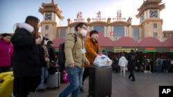 Para wisatawan mengenakan masker saat berjalan keluar dari stasiun kereta api di Beijing, Senin, 20 Januari 2020.
