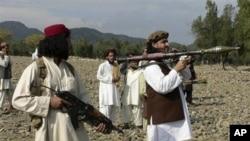 ຜູ້ນຳຂອງພວກກະບົດຕາລີບານໃນປາກິສຖານ ນາຍ Hakimullah Mehsud (ຂວາ) ແບກປືນຍິງຈະຫຼວດໝາກປີ ໃນເຂດຊົນເຜົ່າ Waziristan ໃຕ້ (4 ຕຸລາ 2009)