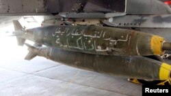 "A Royal Jordanian Air Force plane bears bombs that say ""the martyr captain and hero pilot Muath al-Kasaesbeh,"" in preparation for strikes on Islamic State militants in Syrian city of Raqqa, Feb. 5, 2015."