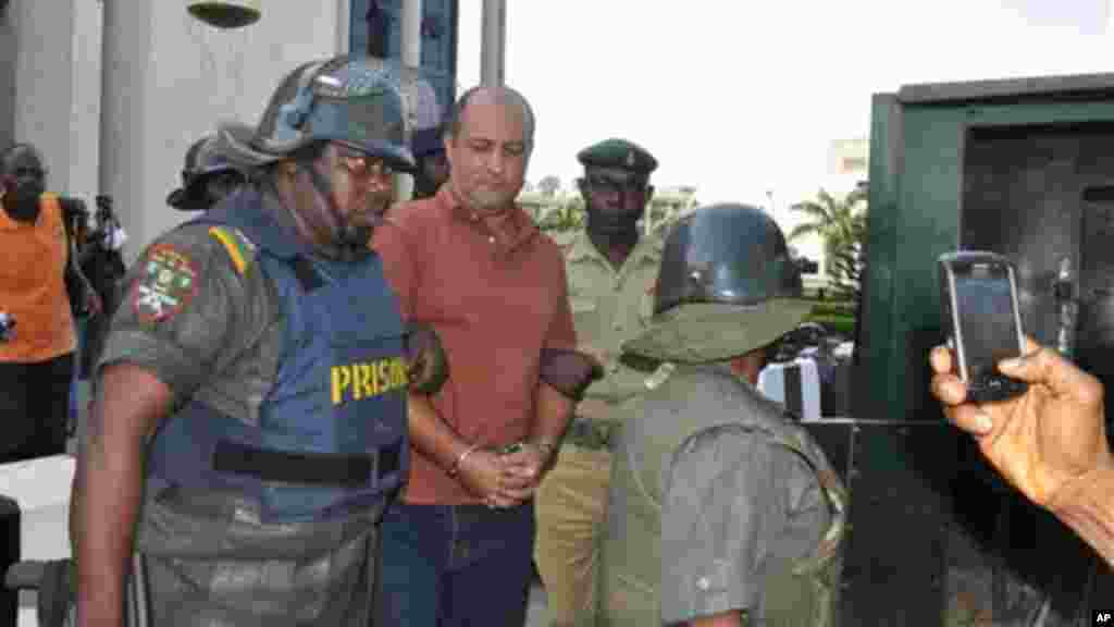 Talal Ahmad Roda, a Nigerian-Lebanese man accused of belonging to Hezbollah, centre, is led out by prison security officers after he was sentenced to life imprisonment at the Federal High Court in Abuja, Nov. 29, 2013.