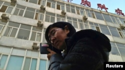 FILE - Wang Yu, the lawyer of human right activist Cao Shunli, talks on the phone in front of a hospital building where Cao was hospitalized at its intensive care unit in Beijing, March 1, 2014.
