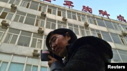 Wang Yu, the lawyer of human right activist Cao Shunli, talks on the phone in front of a hospital building where Cao is hospitalized at its intensive care unit in Beijing, March 1, 2014.