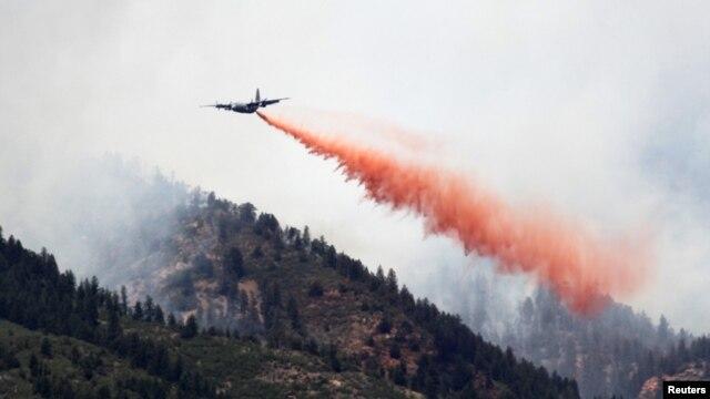 Un avión militar C-130 deja caer sobre las llamas miles de galones de retardador de incendios.