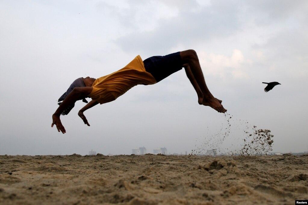 인도 코치의 해변에서 어린 소년이 재주넘기를 연습하고 있다.