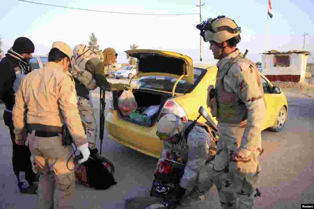 Security personnel search the vehicle of a resident who is fleeing violence in Anbar province at a checkpoint in Ein Tamarm, Jan. 6, 2014.