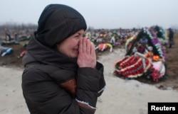 Người thân của nạn nhân thiệt mạng do trúng pháo khóc thương tại một nghĩa trang ở thành phố cảng Mariupol, Ukraine, 27/1/2015.