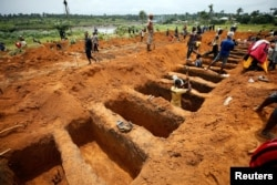 Workers dig graves for mudslide victims at the Paloko cemetery in Waterloo, Sierra Leone, Aug. 17, 2017.