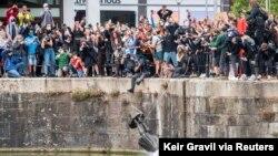 Tượng Edward Colston bị thả xuống hồ nước sau khi bị kéo xuống ở Bristol, Anh, hôm 7 tháng Sáu. (Keir Gravil via Reuters)