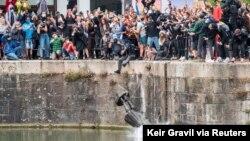 Demonstran anti-rasisme di Bristol, Inggris mencampakkan patung Edward Colston ke dalam air pada aksi protes hari Minggu (7/6).