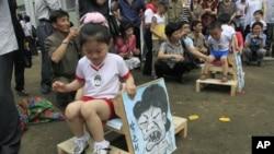 지난해 6월 북한 평양에서 열린 국제 아동절 기념 행사에서 어린이들이 박근혜 한국 대통령과 바락 오바마 미국 대통령을 그린 인물화를 깔고 앉는 게임을 하고 있다. (자료사진)