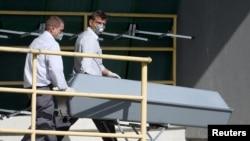 Một chiếc quan tài được đưa lên xe tải tại một tòa nhà hải quan tại làng Nickelsdorf, Áo, nơi xác của 71 di dân được tìm thấy trên một chiếc xe tải trên một xa lộ gần biên giới Hungary.