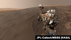 """FILE - This self-portrait of NASA's Curiosity Mars rover shows the vehicle at """"Namib Dune,"""" where the rover's activities included scuffing into the dune with a wheel and scooping samples of sand for laboratory analysis."""