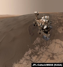 """This self-portrait of NASA's Curiosity Mars rover shows the vehicle at """"Namib Dune,"""" where the rover's activities included scuffing into the dune with a wheel and scooping samples of sand for laboratory analysis."""