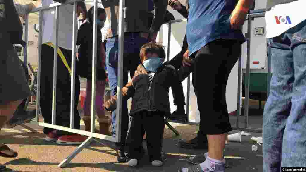 Un niño es visto de la mano de una mujer en un albergue improvisado en Tijuana, donde se encuentran los migrantes esperando entrar a EE.UU. Fotografía: Celia Mendoza- VOA