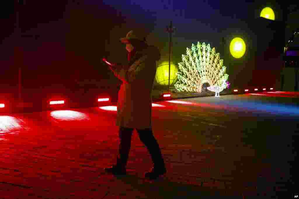 Un hombre camina el 31 de diciembre de 2019 cerca a una escultura de luz antes del conteo de año nuevo en el las instalaciones de los Juegos Olímpicos de Invierno de Bejing (2022).