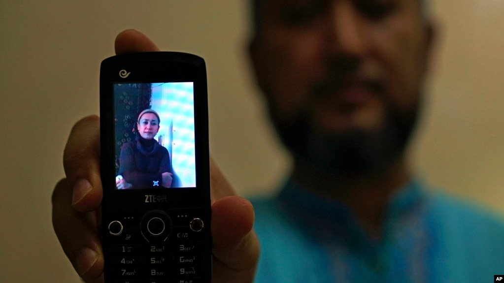 Halmurat Idris holds up a picture of his elder sister, Aug. 24, 2018, at his home in Istanbul, Turkey. Idris says his sisters were monitored as part of a government homestay program, part of a broader crackdown on religious expression in China's far western region of Xinjiang.