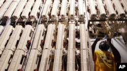 Verizon special service technician Mark Rose adjusts cables attached to a framework in a Verizon network room at the Main Post Office in New York. (File photo)