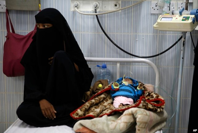 A woman sits next to her malnourished baby at a therapeutic feeding center in a hospital in Sanaa, Yemen, Jan. 24, 2016.