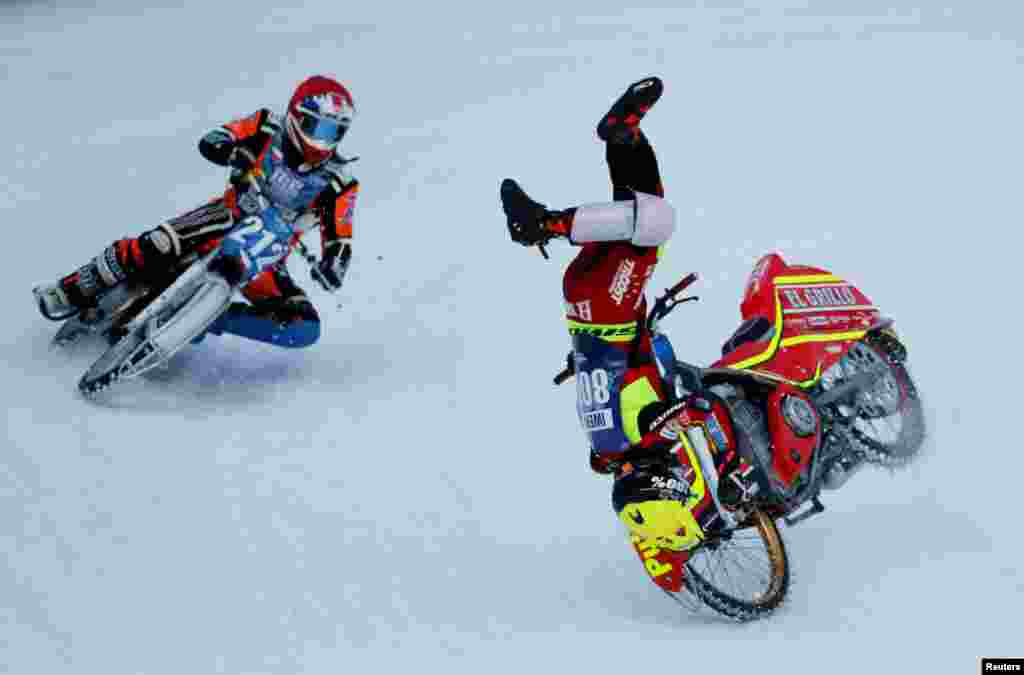 Jasper Iwema of Netherlands falls down while competing with Lukas Hutla of Czech Republic during the final round of the FIM Ice Speedway Gladiators World Championship at the Medeo rink in Almaty, Kazakhstan.
