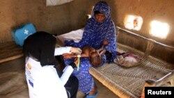 یمن میں ایک رضاکار غذائی قلت کی شکار ایک بچی کا معائنہ کر رہی ہے (فائل فوٹو)