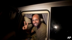 Saif al-Islam, son of Moammar Gadhafi, makes a peace sign before meeting reporters in Tripoli, Libya, Aug. 23, 2011.