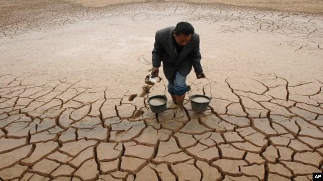 A farmer takes water form a dried-up pond to water his vegetable field on the outskirts of Yingtan, Jiangxi province December 10, 2007. Climate change has been blamed for more frequent droughts in some regions.