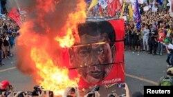 Warga Filipina melakukan demonstrasi dengan membakar kubus bergambar Presiden Rodrigo Duterte dalam aksi di luar istana Presiden di Manila, 21 September lalu.