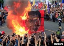 지난달 21일 필리핀 마닐라 대통령궁 인근에 모인 시민들이 로드리고 두테르테 대통령 초상화를 불태우고 있다.