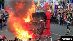 Protesters burn a cube effigy with a face of President Rodrigo Duterte during a National Day of Protest outside the presidential palace in metro Manila, Philippines Sept. 21, 2017.