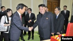 정전 60주년 기념 '전승절' 행사에 참석하기 위해 방북한 리위안차오 중국 국가부주석(왼쪽)이 26일 김정은 북한 국방위원회 제1위원장과 만나 악수하고 있다.