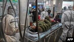 身穿防护服的医务人员在武汉红十字医院运送一名病人。(2020年1月25日)