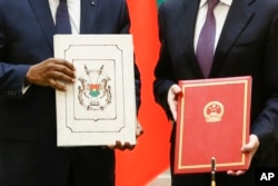 China's Foreign Minister Wang Yi, right, and Burkina Faso Foreign Minister Alpha Barry display documents establishing diplomatic relations between the two countries in Beijing, May 26, 2018.
