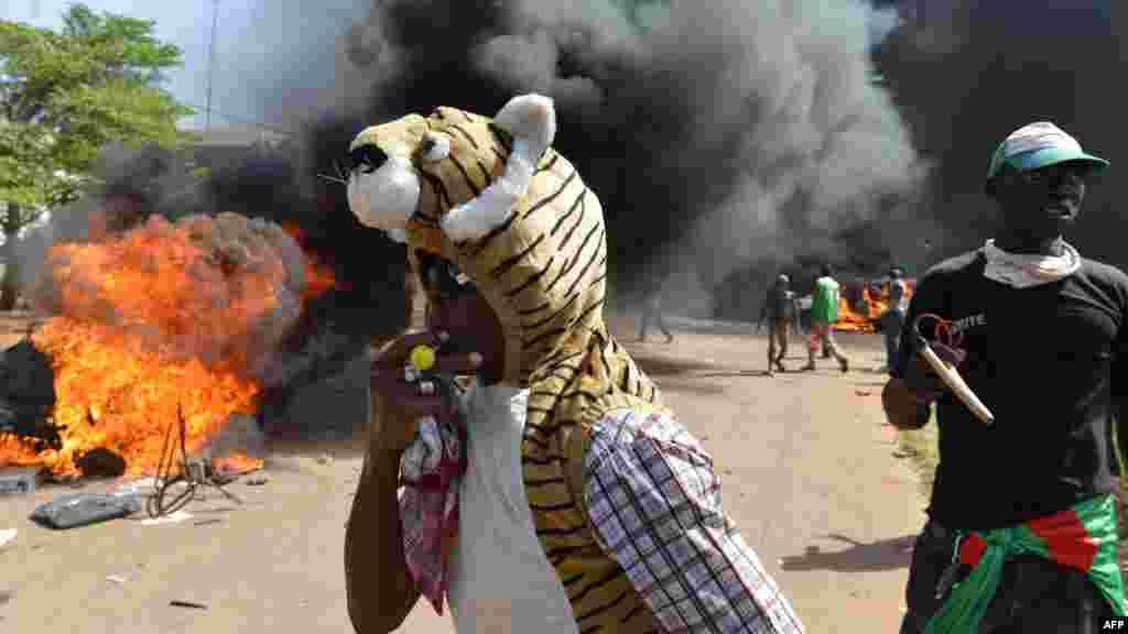 Les manifestants se tiennent devant le parlement où des voitures et des documents brulent, à Ouagadougou le 30 Octobre, 2014. Des centaines de manifestants en colère au Burkina Faso ont pris d'assaut le parlement le 30 Octobre avant d'y mettre le feu en signe de protestation contre l'intention de modifier la Constitution pour permettre au Président Blaise Compaoré pour étendre son règne de 27 ans. AFP PHOTO / ISSOUF SANOGO
