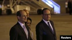 ປະທານາທິບໍດີ ຝຣັ່ງ ທ່ານ Francois Hollande (ຂວາ) ຍ່າງຄຽງຂ້າງ ຮອງລັດຖະມົນຕີຕ່າງປະເທດ ຄິວບາ ທ່ານ Rogelio Sierra (ຊ້າຍ) ຢູ່ທີ່ສະໜາມບິນນານາຊາດ ນະຄອນຫຼວງ ຮາວານາ, ວັນທີ 10 ພຶດສະພາ 2015.