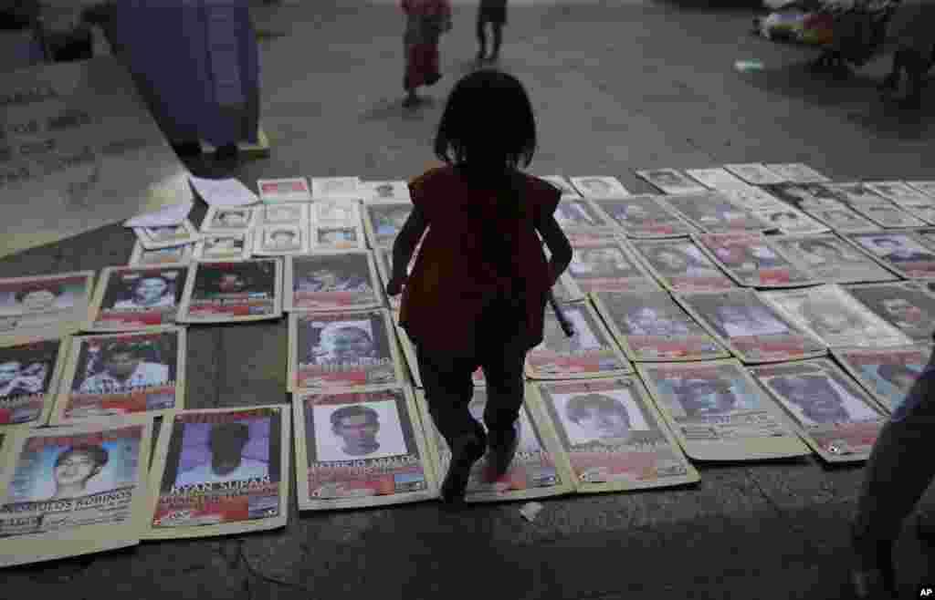 Uma menina filipina caminha por cima de fotos de pessoas desaparecidas durante um ajuntamento de familiares de activistas desaparecidos em Manila, Filipinas, no dia dos Finados.