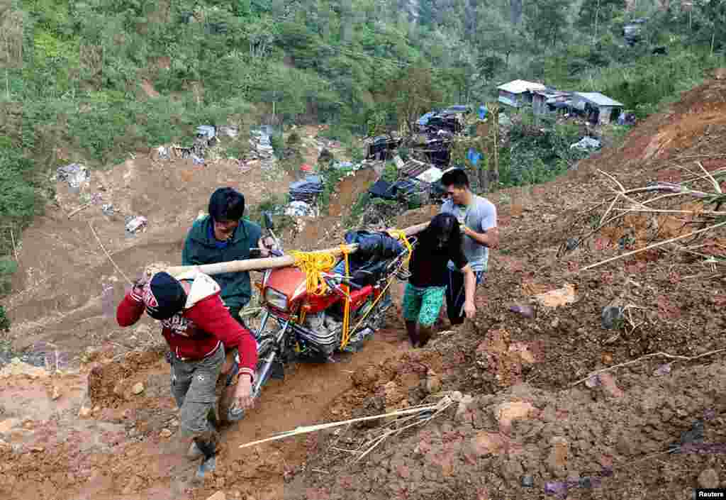 Residents carry a motorcycle on a road damaged by a landslide from Typhoon Mangkhut at a small-scale mining camp in Itogon, Benguet, in the Philippines.
