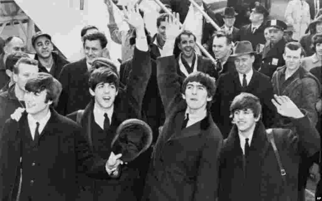 Kundi la Beatles likipungia wapenzi wa muziki baada ya kuwasili uwanja wa ndege wa Kennedy, New York mwaka 1964.