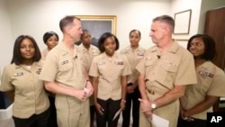Yeoman First Class LaToya Jones, center, speaks as Chief of Naval Operations Adm. John Richardson, left of center, and Chief of Naval Personnel Adm. Robert Burke, right of center, and other members of the working group listen. The Navy says it will now allow servicewomen to sport ponytails and other hairstyles, reversing a policy that long forbade females from letting their hair down, in a frame grab from a Facebook Live event, July 10, 2018.