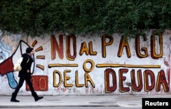 "FILE - A woman walks past a graffiti that reads ""No to the debt payment"" in Buenos Aires, July 28, 2014."