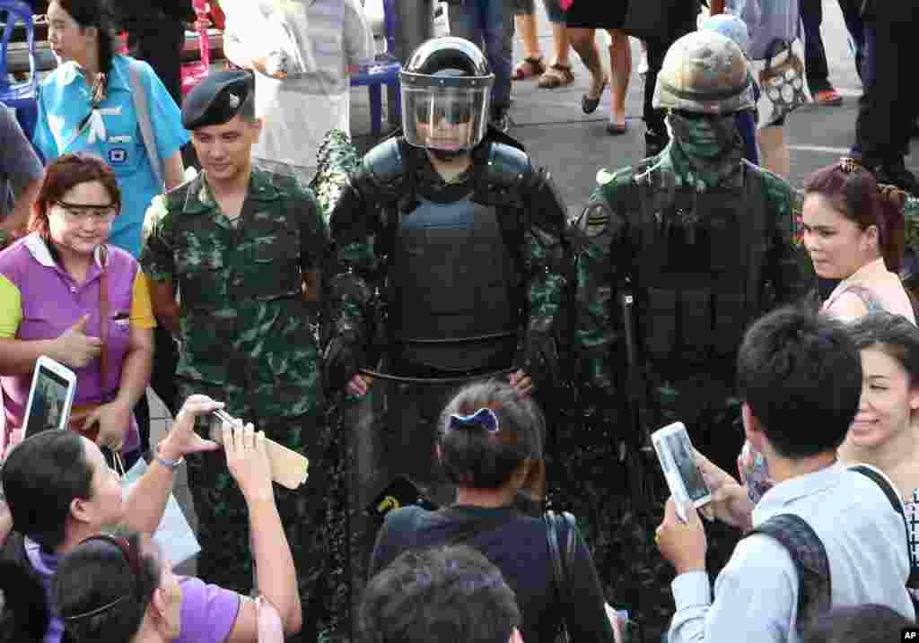 People take photos of Thai special forces officers during an event called 'Return Happiness to Thai People' at Bangkok's Victory Monument, June 4, 2014.