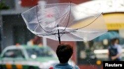 28일 태풍 '종다리'가 상륙한 일본 도쿄에서 행인이 든 우산이 강풍에 뒤집혔다.