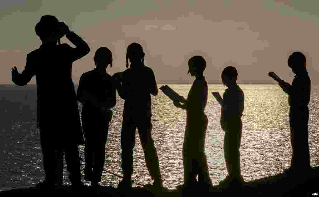 "Ultra-Orthodox Jewish boys pray along the Mediterranean Sea in the Israeli city of Herzliya, near Tel Aviv, while performing the ""Tashlich"" ritual during which ""sins are cast into the water to the fish."""