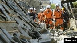 Tim penyelamat dan pemadam kebakaran Jepang memeriksa rumah-rumah yang ambruk akibat gempa di kota Mashiki, Kumamoto, Jepang selatan.