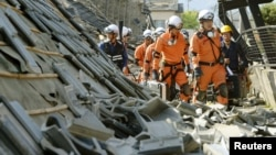 Firefighters walk among collapsed houses caused by an earthquake in Mashiki town, Kumamoto prefecture, southern Japan, in this photo taken by Kyodo, April 15, 2016. (REUTERS/Kyodo)