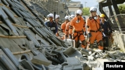 FILE - Firefighters walk among collapsed houses caused by an earthquake in Mashiki town, Kumamoto prefecture, southern Japan, April 15, 2016.