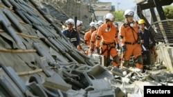 Nhân viên cứu hỏa làm việc trên những ngôi nhà đổ nát sau trận động đất ở thị trấn Mashiki, Nhật Bản, ngày 15/4/2016.